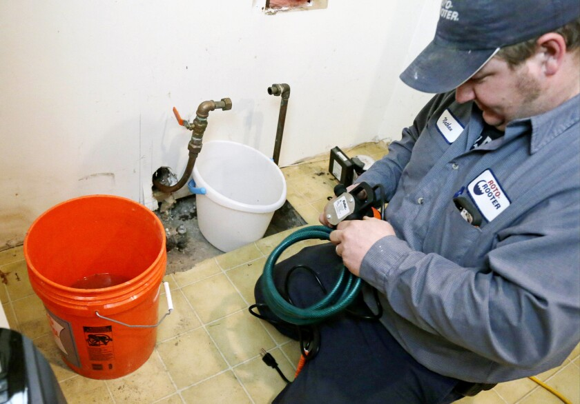 """Plumber Nate Petersen prepares a pump to shoot water into the incoming city water line, left pipe, that has been frozen Thursday, Jan. 9, 2014, at a south Minneapolis home. Roto Rooter was been """"inundated"""" with calls since the cold snap and regular work has been put on hold because of burst pipes and even frozen sewer lines according to plumbing manager Paul Teale. The deep freeze and storms that gripped much of the country over the past week cost the economy as much as $5 billion, by one estimate. (AP Photo/Jim Mone)"""