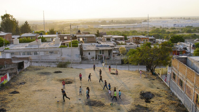 Residents of Lo De Juarez, a small community in Guanajuato play soccer. In the background is a Ford