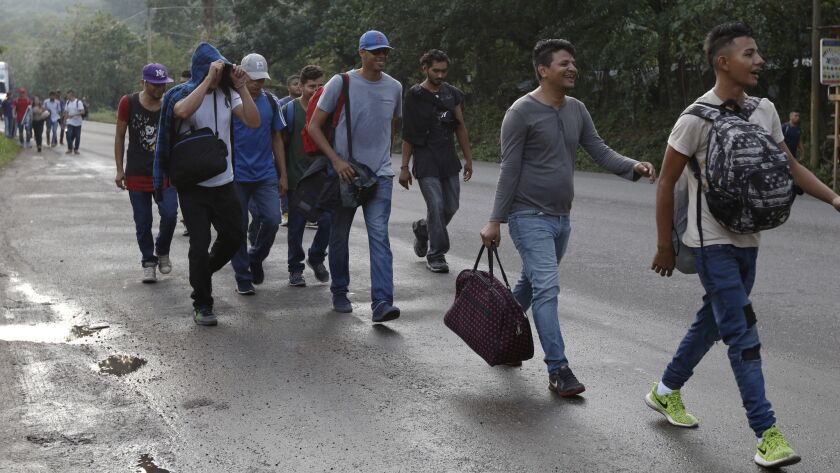 U.S.-bound migrants walk along the roadside as they leave Cofradia, Honduras, early Tuesday, Jan. 15