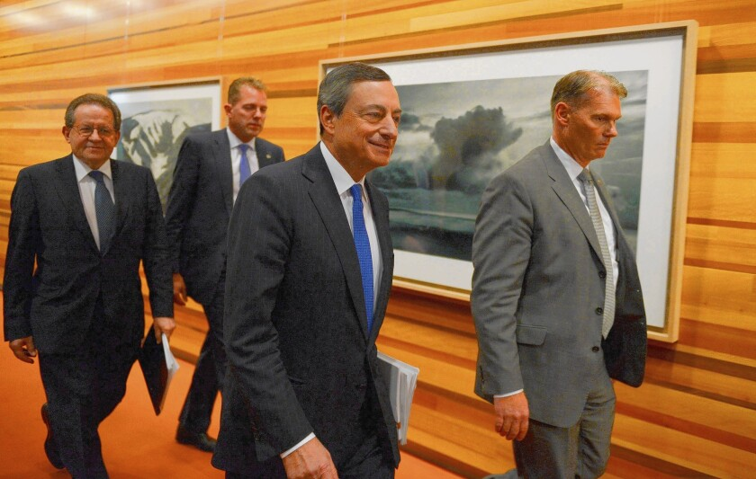 European Central Bank President Mario Draghi, center foreground, arrives for a news conference in Frankfurt, Germany.