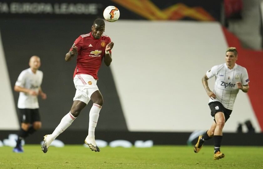Manchester United's Paul Pogba heads the ball during the Europa League round of 16 second leg soccer match between Manchester United and LASK at Old Trafford in Manchester, England, Wednesday, Aug. 5, 2020. (AP Photo/Dave Thompson)