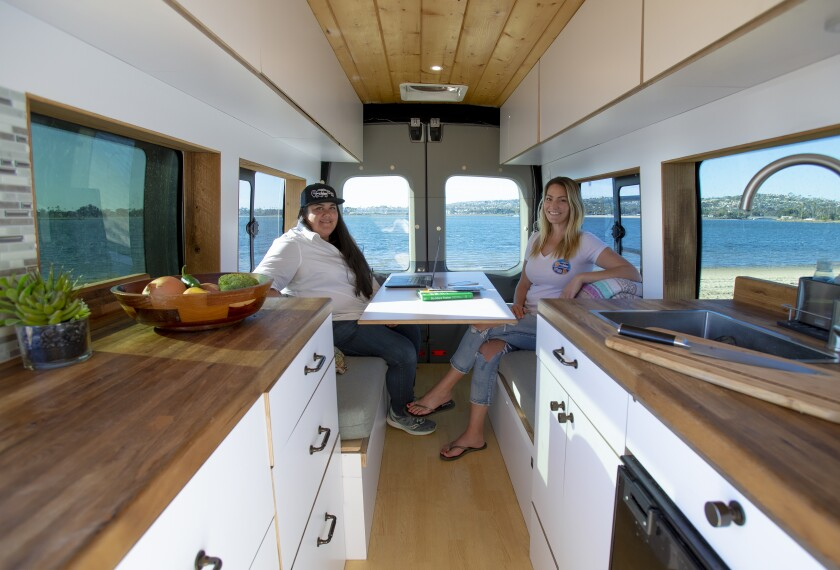 Breanne Acio (left) and Jessica Shisler, co-founders of The Vanlife App, relax in Acio's converted van after a business meeting.