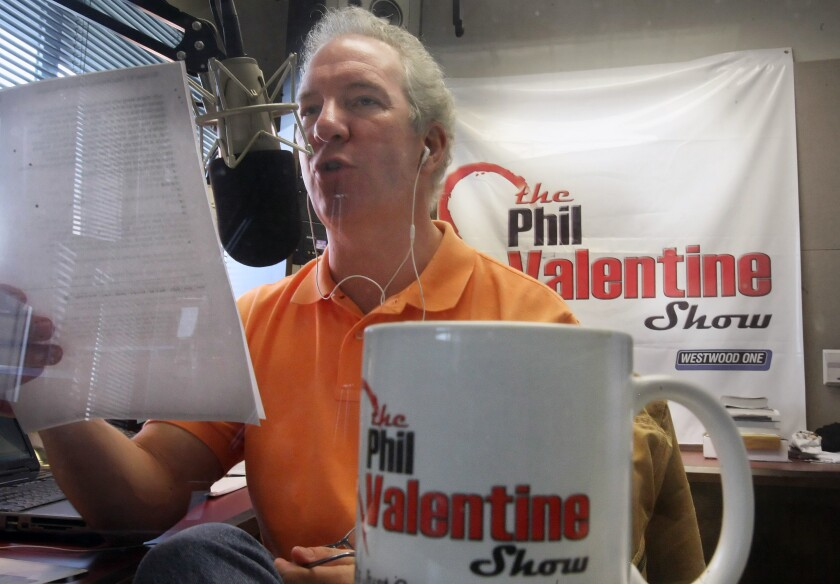 Phil Valentine in front of a microphone with a coffee cup and sign saying The Phil Valentine Show