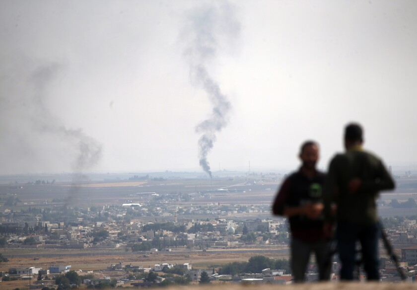 Smoke above Ras al-Ayn in Syria serves as the backdrop for TV journalists in Ceylanpinar, Turkey, on Sunday.