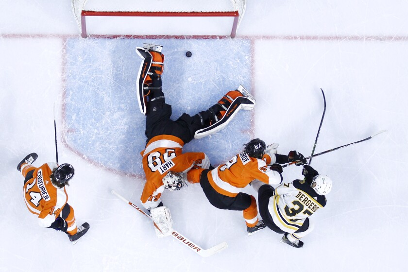 Boston Bruins' Patrice Bergeron, right, scores a goal past Philadelphia Flyers goaltender Carter Hart (79) as Ivan Provorov (9) and Sean Couturier (14) defend during the first period of an NHL hockey game, Tuesday, April 6, 2021, in Philadelphia. (AP Photo/Derik Hamilton)
