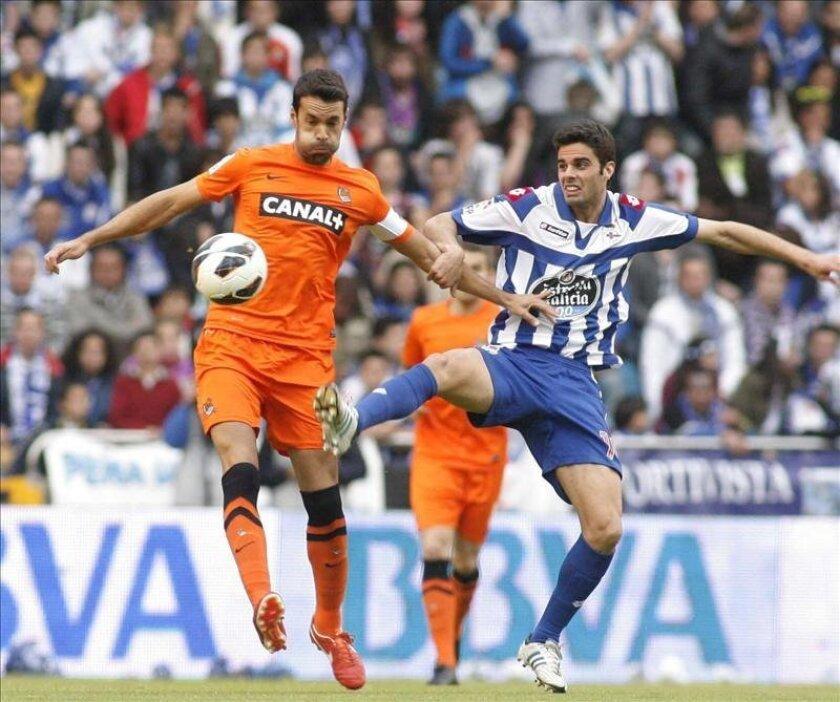 El centrocampista de la Real Sociedad Xabi Prieto (i) lucha un balón con Juan Domínguez, del Deportivo de la Coruña, durante el encuentro de la última jornada de Liga disputado  el sábado en el estadio de Riazor. EFE