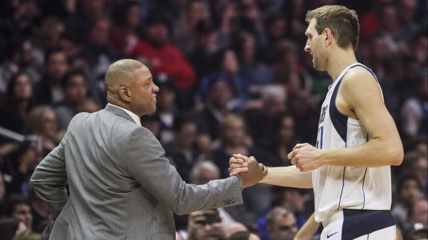 Clippers coach Doc Rivers greets Mavericks forward Dirk Nowitzki during a break in the action at Staples Center.