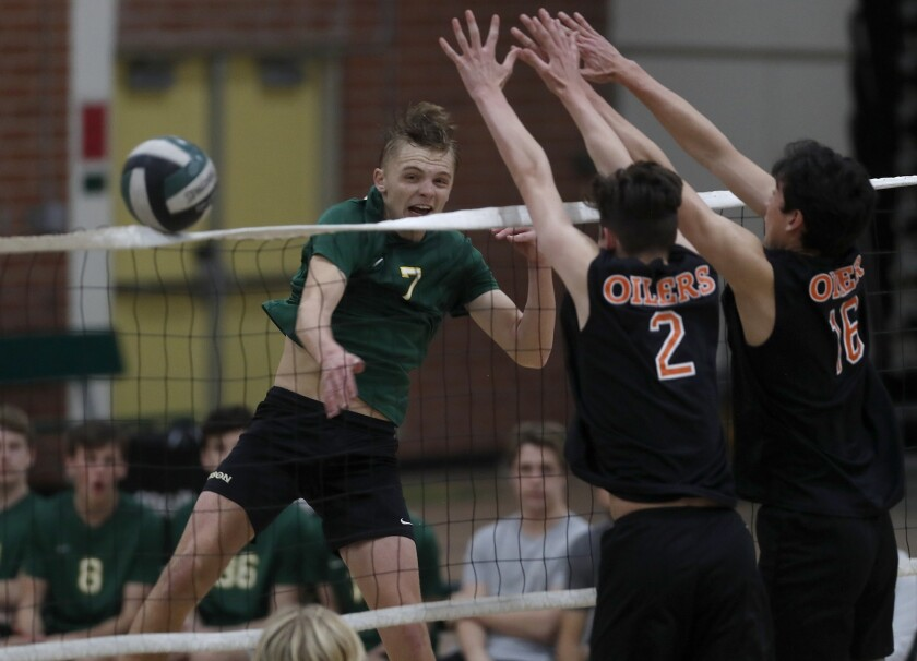 Edison High's James Carpenter, left, hits against Huntington Beach during the fourth set in a Sunset