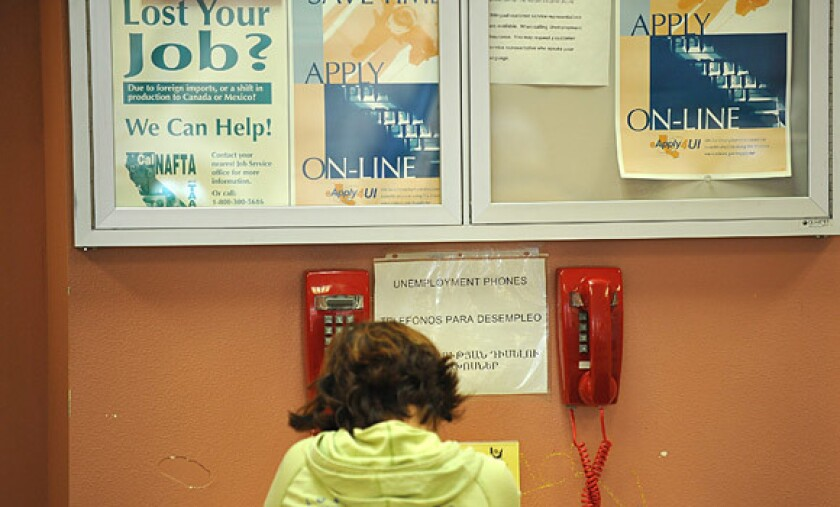 A woman uses a telephone at a job center in Glendale to apply for unemployment benefits.