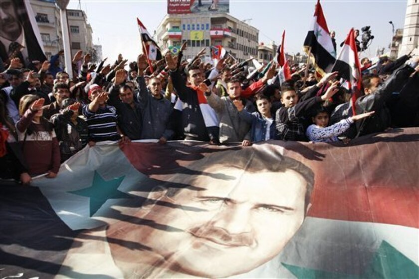 Syrians hold a large poster depicting Syria's President Bashar Assad during a rally in Damascus, Syria, Monday, Dec. 19, 2011. Syria signed an Arab League initiative Monday that will allow Arab observers into the country as part of peace deal that aims to end the nation's increasingly bloody 9-mont