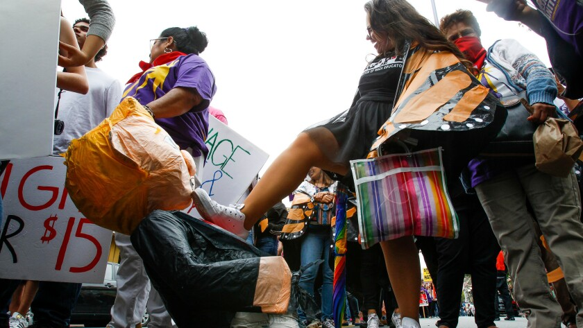 A woman steps on a piñata version of presidential candidate Donald Trump as she and a group of anti-Trump protesters march through downtown San Diego on May 27.