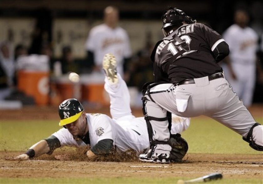 Oakland Athletics' Daric Barton, left, slides to score as Chicago White Sox catcher A.J. Pierzynski (12) misses the catch at home plate during the third inning of a baseball game Tuesday, Sept. 21, 2010, in Oakland, Calif. Barton scored on a double by Kurt Suzuki. (AP Photo/Ben Margot)