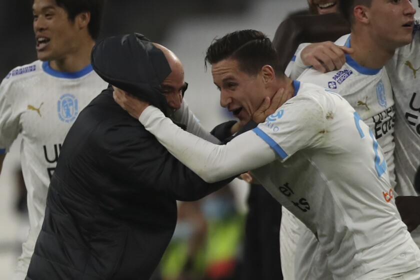 Marseille's Florian Thauvin, right, celebrates with Marseille's coach Jorge Sampaoli after scoring his side's second goal during the French League One soccer match between Marseille and Brest at the Stade Veledrome stadium in Marseille, France, Saturday, March 13, 2021. (AP Photo/Daniel Cole)