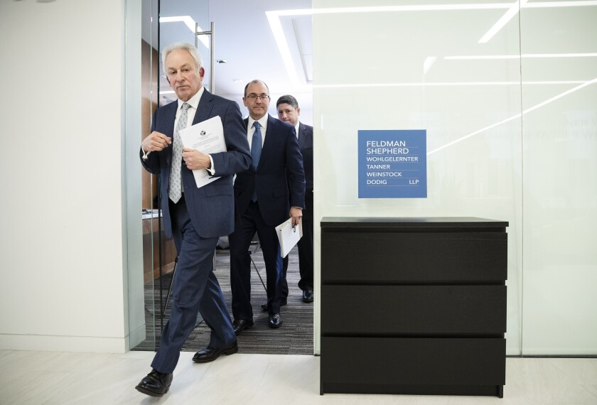 Attorneys representing the Dudek family, Alan Feldman, left, Daniel Mann, and Edward Goldis walk from a news conference, past IKEA's Malm dresser in Philadelphia, Monday, Jan. 6, 2020. IKEA has agreed to pay $46 million to the parents of a 2-year-old boy who died of injuries suffered when a 70-pound recalled dresser tipped over onto him, the family's lawyers said Monday. (AP Photo/Matt Rourke)