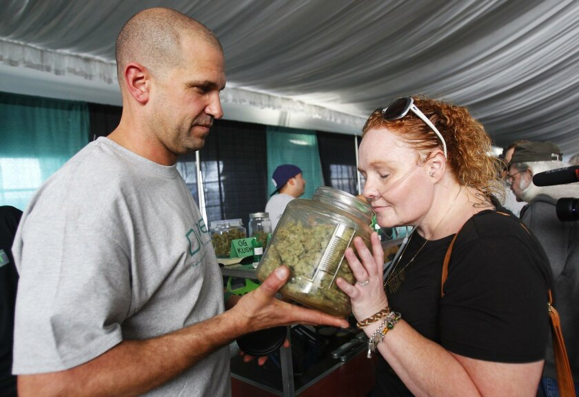 Alicia Tucker, right, smells a strain of marijuana held by Robert Kirk of Duber Collective, one of the exhibitors at PotLuck, a medical cannabis expo.