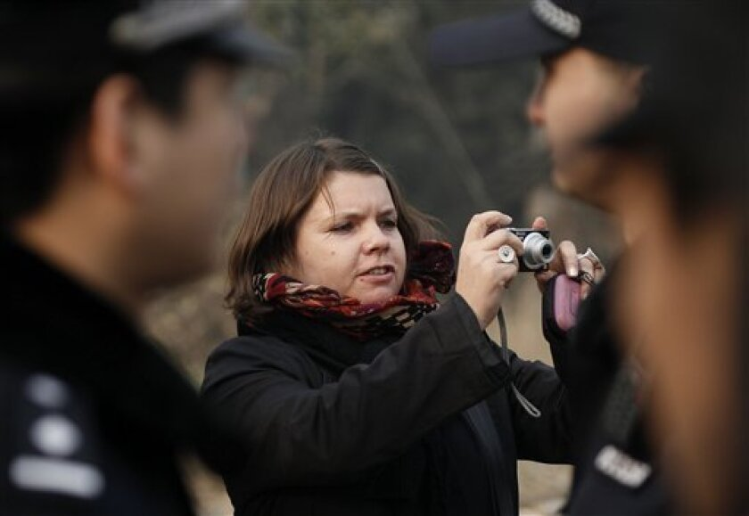 Karen Patterson of Canada, center,  wife of Chinese artist Wu Yuren, takes pictures of her supporters after attending her husband's trial at the Wenyuhe Court in Beijing, China Wednesday, Nov. 17, 2010. Wu was detained and charged after he helped organize protests near Tiananmen Square against some