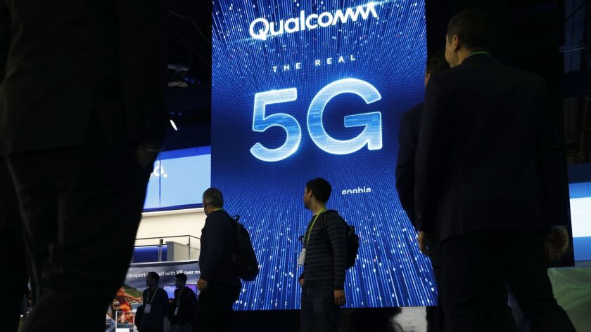 FILE- In this Jan. 9, 2019, file photo a sign advertises 5G at the Qualcomm booth at CES Internation