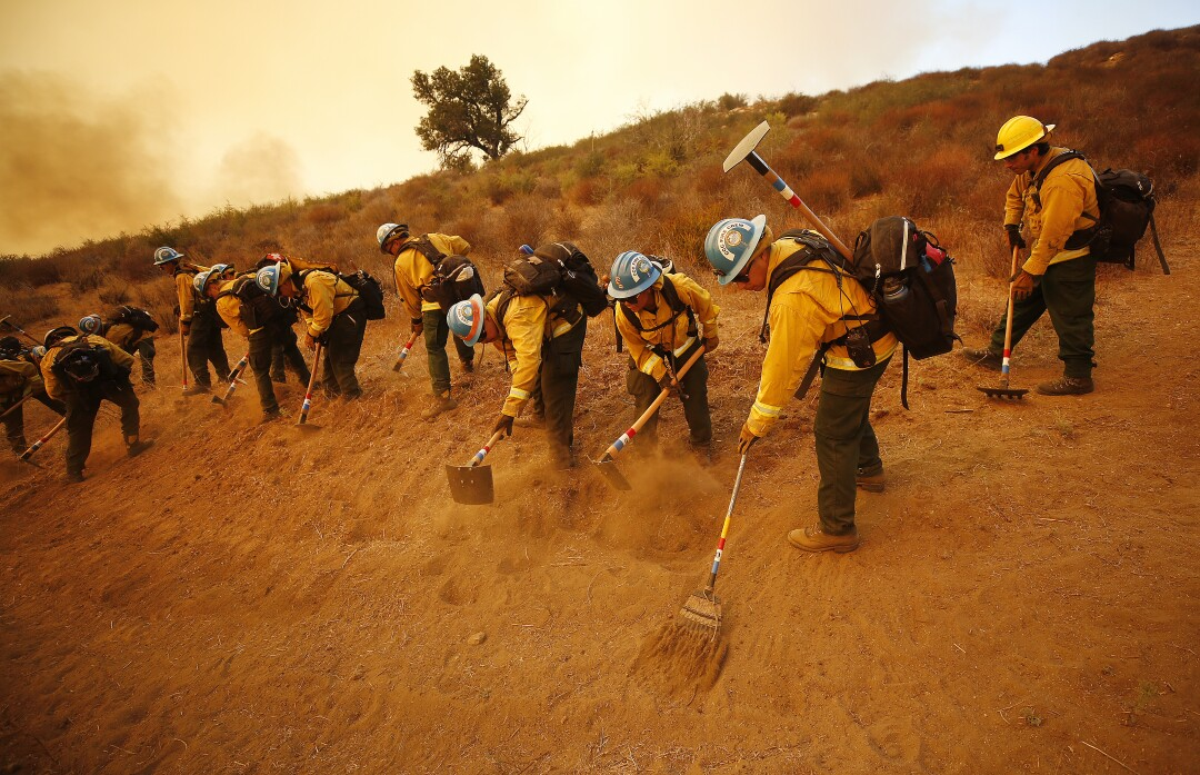 Firefighters rake up earth.