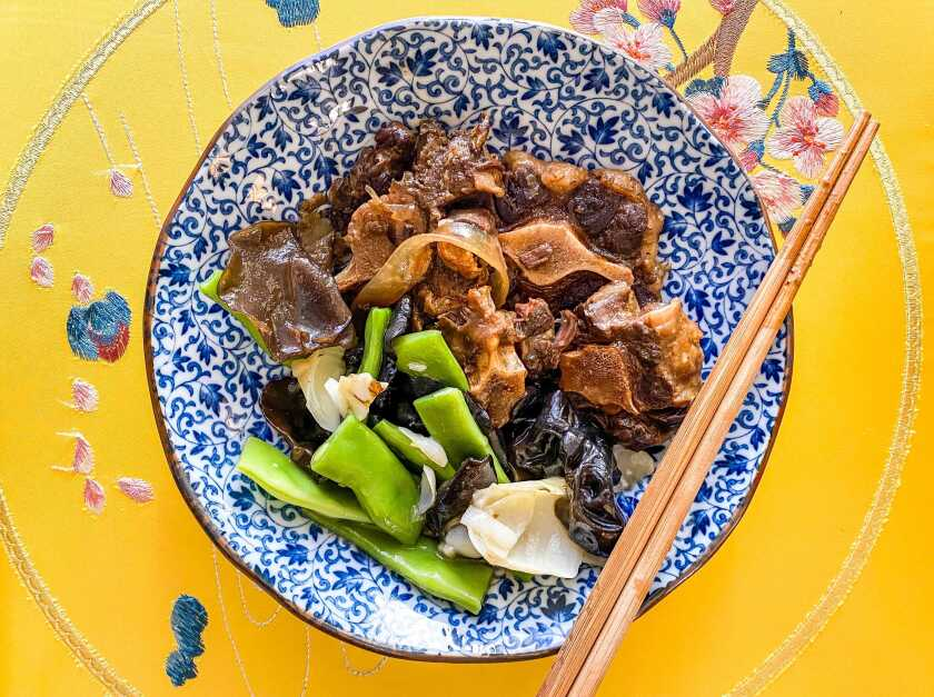 A bowl filled with oxtails in black bean sauce over glass noodles with stir-fried vegetables.