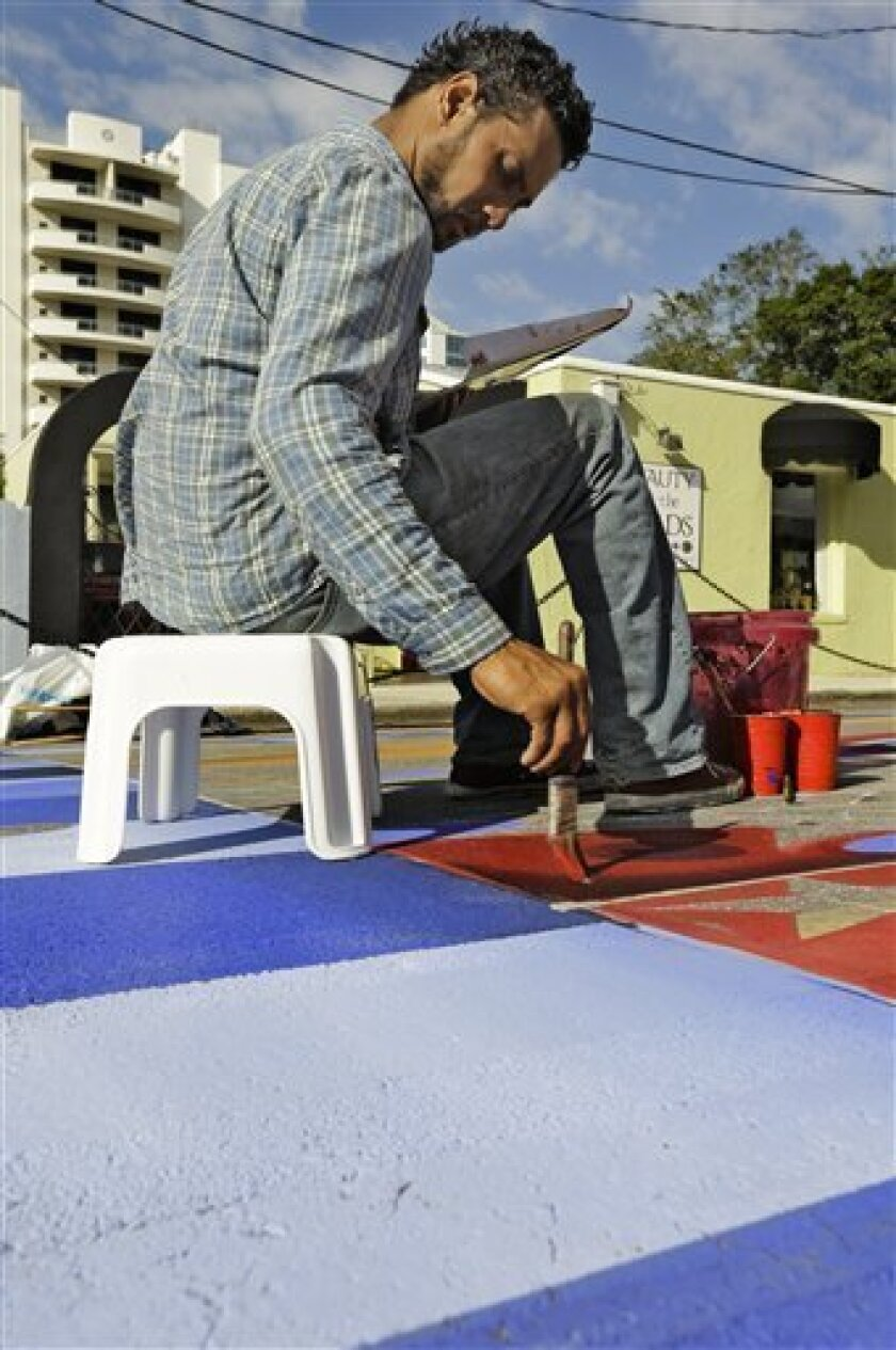 Agnaldo Eduardo Kobra, of Brazil, works on his 3D pavement art during the Sarasota Chalf Festival Wednesday, Oct. 31, 2012, in Sarasota, Fla. The annual festival begins this week and runs through Nov. 6.(AP Photo/Chris O'Meara)