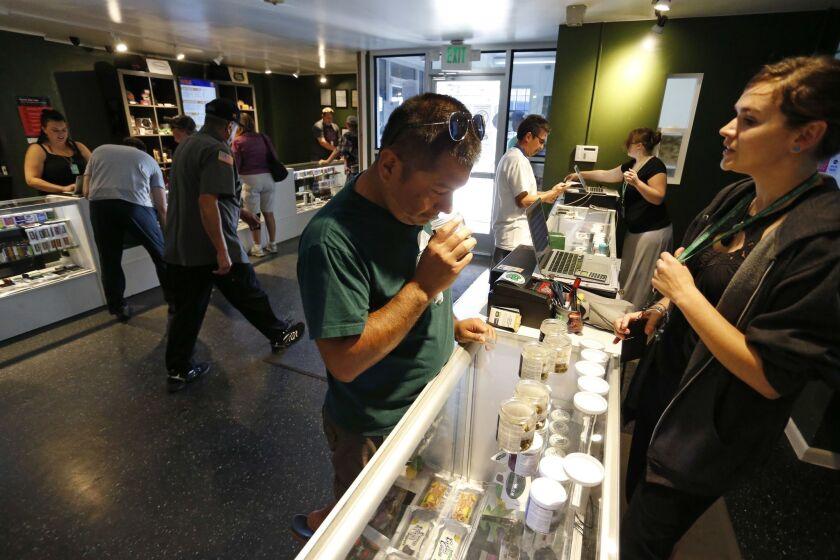 Customers shop for marijuana inside a recreational marijuana store in Denver in 2015. Sen. Elizabeth Warren (D-Mass.) is leading an effort to make sure vendors working with marijuana businesses don't have their banking services taken away.