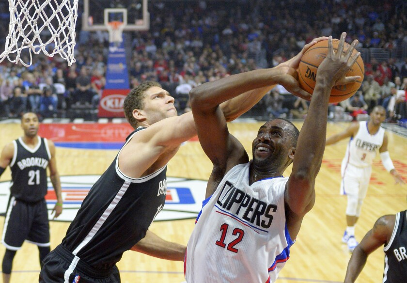 Nets center Brook Lopez, left, tries to block a shot by Clippers forward Luc Mbah a Moute on Feb. 29.