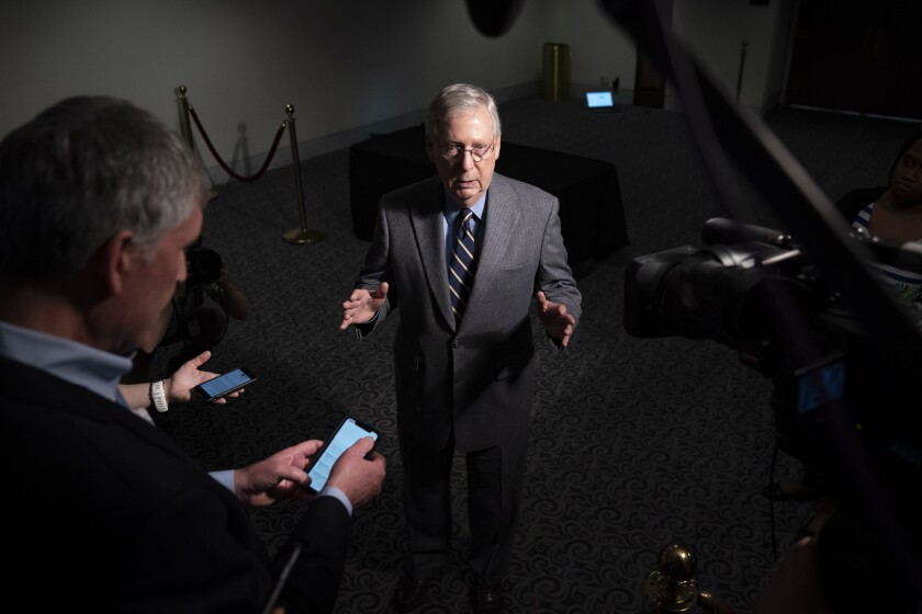 Senate Majority Leader Mitch McConnell (R-Ky.) speaks to reporters after a meeting on the massive economic rescue package that passed the Senate Wednesday.