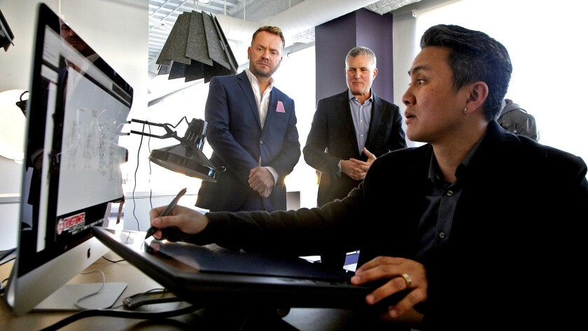 Hasbro executives Simon Waters (Global Brand Licensing) and Steve Davis (Chief Content Officer) watch Walter Gatus, character and Prop designer supervisor, as he works on a Transformers character.