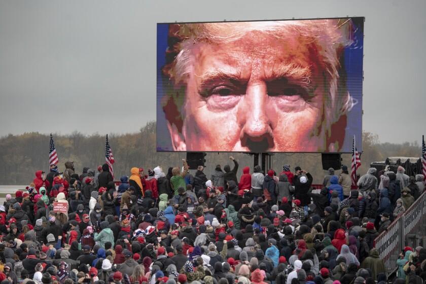 Partidarios del presidente Donald Trump miran una pantalla de video en un evento de campaña