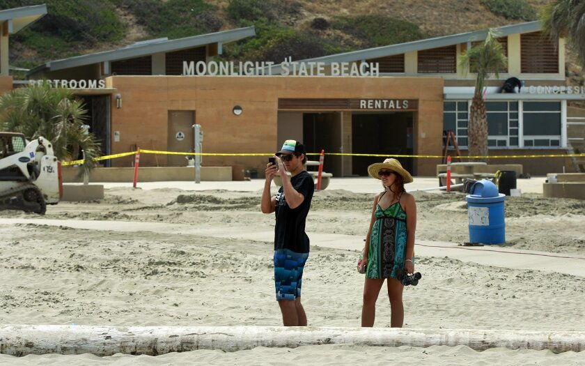 Alex Anshus and his sister Jackie take a picture at Moonlight State Beach. Construction on new showers, restrooms, fire pits, picnic tables, walkways and other facilities at the Encinitas beach will be completed in time for the Memorial Day.