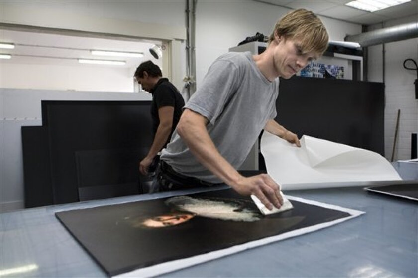 Jouke ter Hofstede of the Van Straaten printing company mounts digital images onto boards to prepare them for an exhibit of images of all paintings by Rembrandt in Boesingheliede, Netherlands, Thursday, June 25, 2009. The images will be displayed at an exhibition of images of all 317 known paintings, 285 etchings and more than 100 drawings by Rembrandt in Amsterdam. The artworks are being reproduced in their true size and have been digitally enhanced by one of the world's leading Rembrandt experts, Ernst van de Wetering, to restore the color and detail they had when they left Rembrandt's studio nearly 400 years ago. The exhibition will start at July 5. (AP Photo/Cynthia Boll)