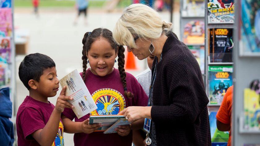 Christopher Medina Gonzalez, left, and Belinda Chegue, 7, show their teacher Melissa Guerin books th