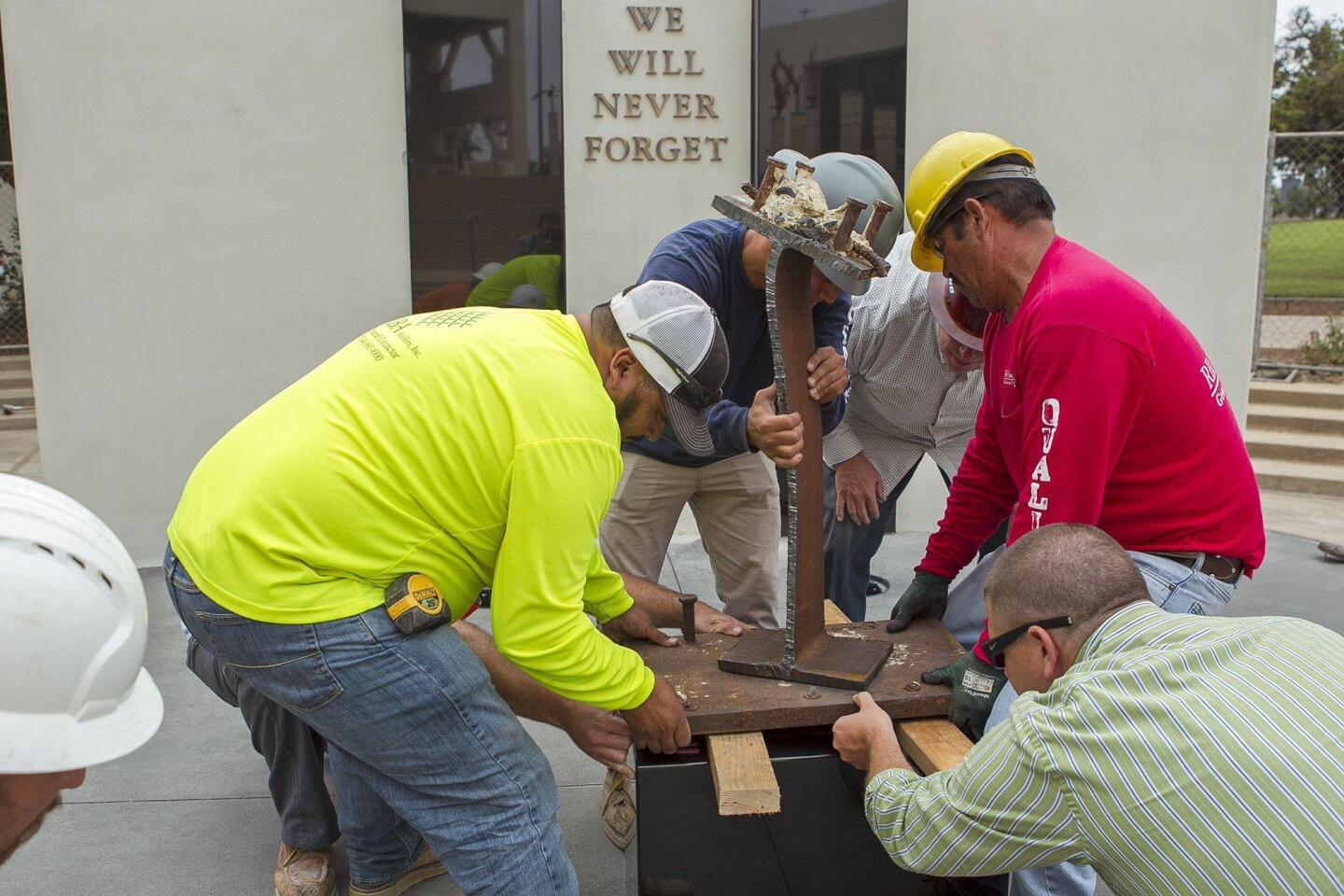 Employees with RBA Builders, Inc. work on the 9/11 memorial outside the Huntington Beach City Hall on Wednesday.
