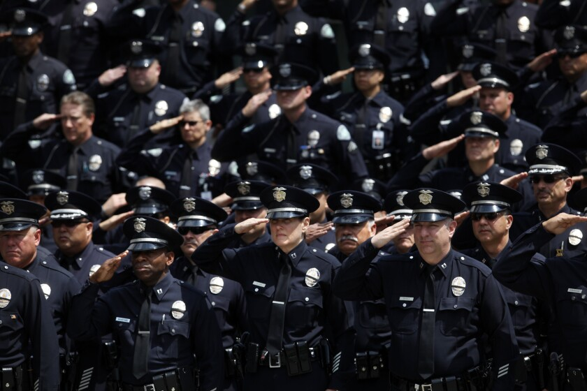 LAPD officers salute during a ceremony at police headquarters in May to honor the more than 200 officers killed over the years in the line of duty.