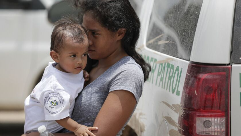 GRANJENO, TEXAS, MONDAY, JUNE 25, 2018 - A woman from Honduras carries her baby, 14 mos., after surr