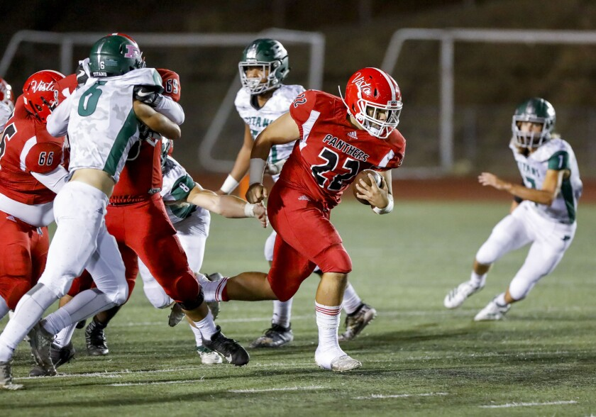 Vista's David Flores (22) busts through the line on his way to a touchdown against Poway on Friday night.