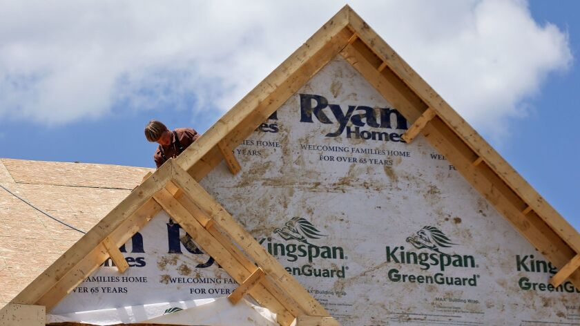 In this Thursday, June 1, 2017, photo, builders work on the roof of a home under construction at a h