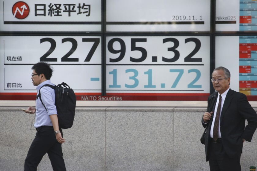 People walk by an electronic stock board of a securities firm in Tokyo, Friday, Nov. 1, 2019. Asian shares were mixed on Friday after investors were spooked by a report that cast doubt on the prospects of a long-term U.S-China trade deal. (AP Photo/Koji Sasahara)