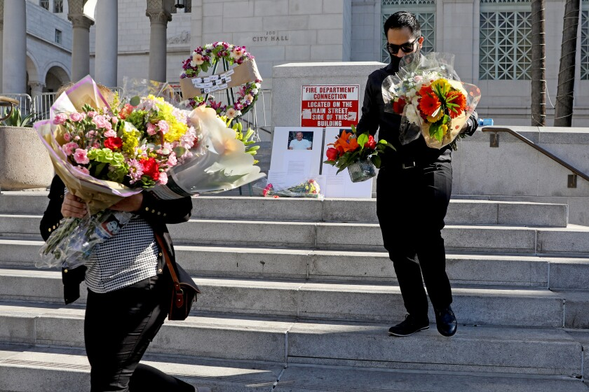 Mourners hold flowers on the steps of City Hall.