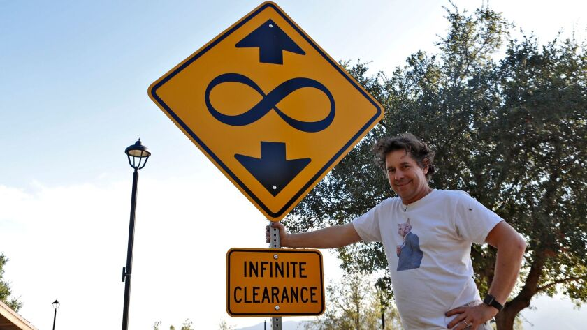 "Artist Scott Froschauer stands next to his ""Infinite Clearance"" street sign artwork at Deukmejian Wi"