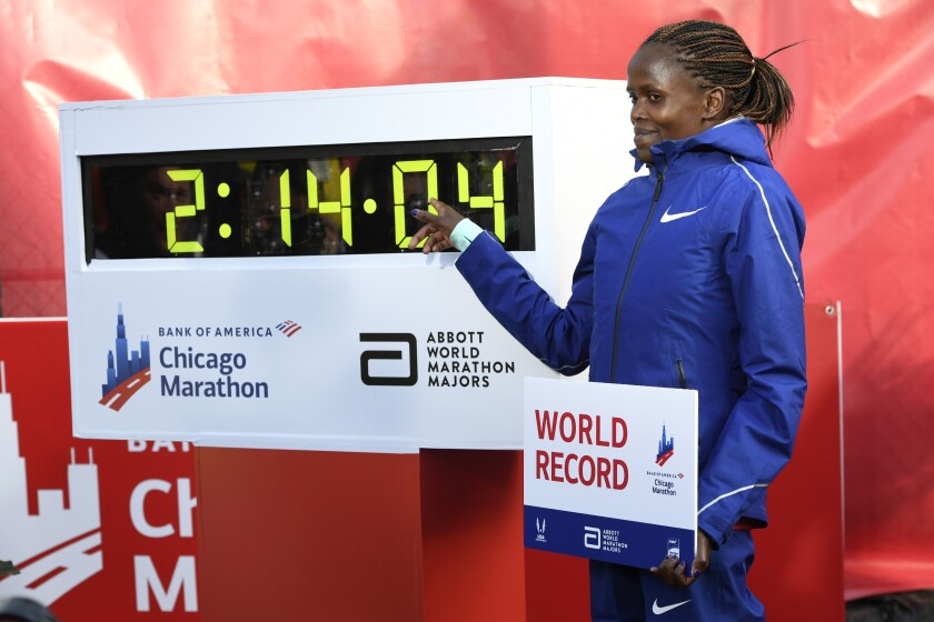 Brigid Kosgei of Kenya poses with her world record-breaking time of 2:14:04 at the 2019 Chicago Marathon.