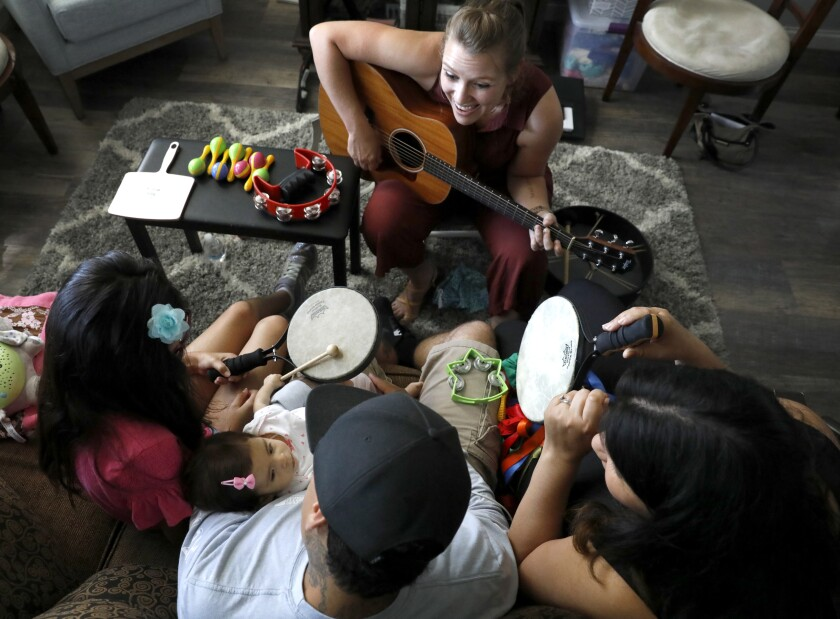 Music therapist Lindsay Zehren, top, does music therapy with the Zaragoza family of Chula Vista. They are, from left: Ava, Ari, Danny and Bianca.