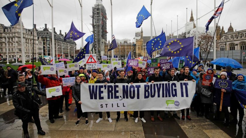 Anti-Brexit activists demonstrate outside the Houses of Parliament in London on March 12, 2019.