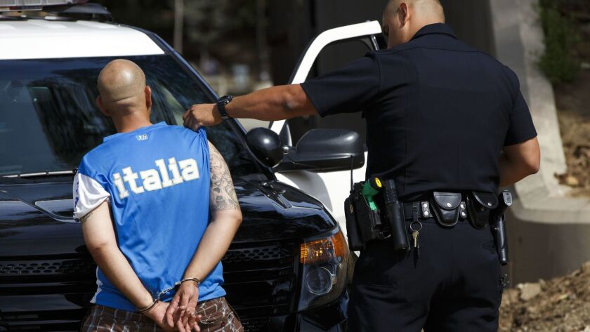 A Los Angeles police officer checks the tattoos for gang affiliations of a parolee arrested on an outstanding warrant at MacArthur Park in 2016.