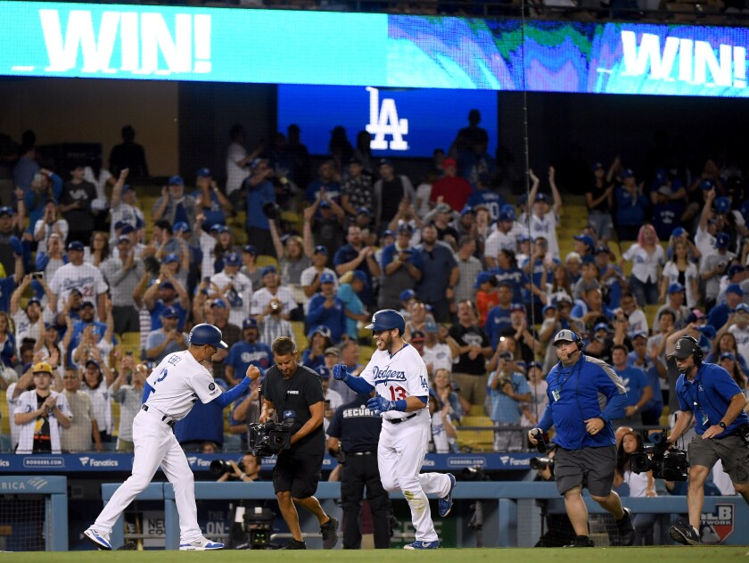 Dodgers' Max Muncy celebrates his walk-off solo homerun with third base coach Dino Ebel to beat the Toronto Blue Jays during the 10th inning at Dodger Stadium on Wednesday.