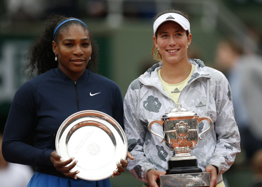 Spain's Garbine Muguruza, right, and Serena Williams of the U.S. hod their trophy after their final match of the French Open tennis tournament at the Roland Garros stadium, Saturday, June 4, 2016 in Paris.  Muguruza won 7-5, 6-4. (AP Photo/Christophe Ena)