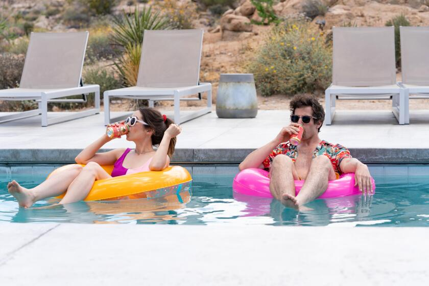 "Cristin Milioti and Andy Samberg float and drink beers in the pool in a scene from ""Palm Springs."""