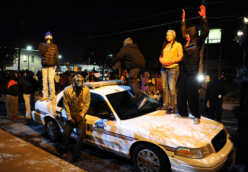 Protesters stand on top of a police car in front of Ferguson City Hall in November, 2014.