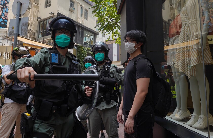 Riot police form a line May 27 as they check pedestrians gathered in the Central district of Hong Kong.