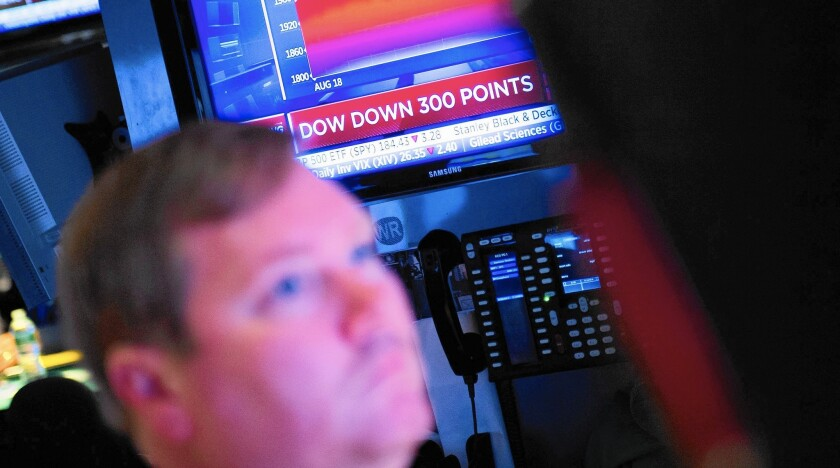 A trader works on the floor of the NYSE at the start of trading Wednesday. After plunging more than 450 points, the Dow ended down 173.45